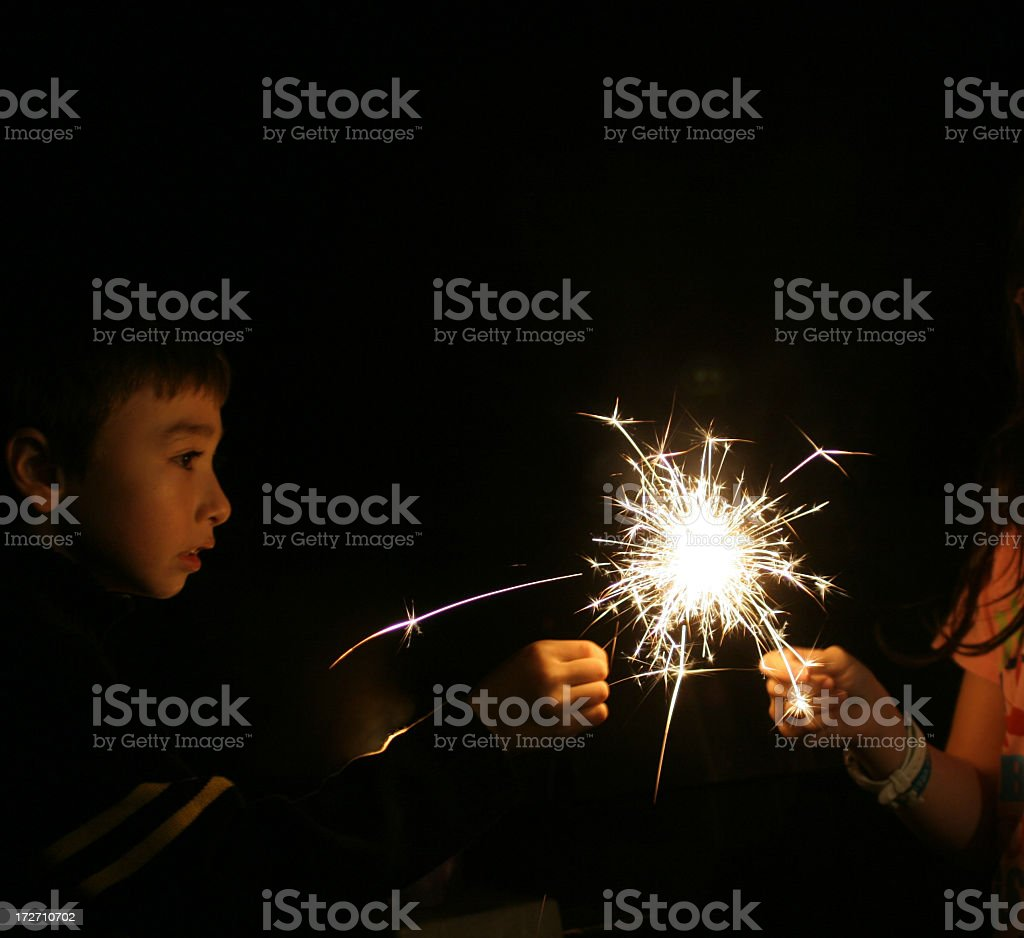 A young boy with a sparkler at night royalty-free stock photo