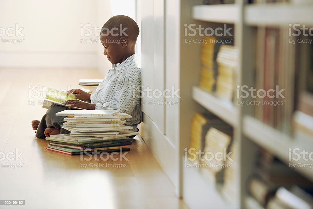 Young boy with a stack of storybooks stock photo