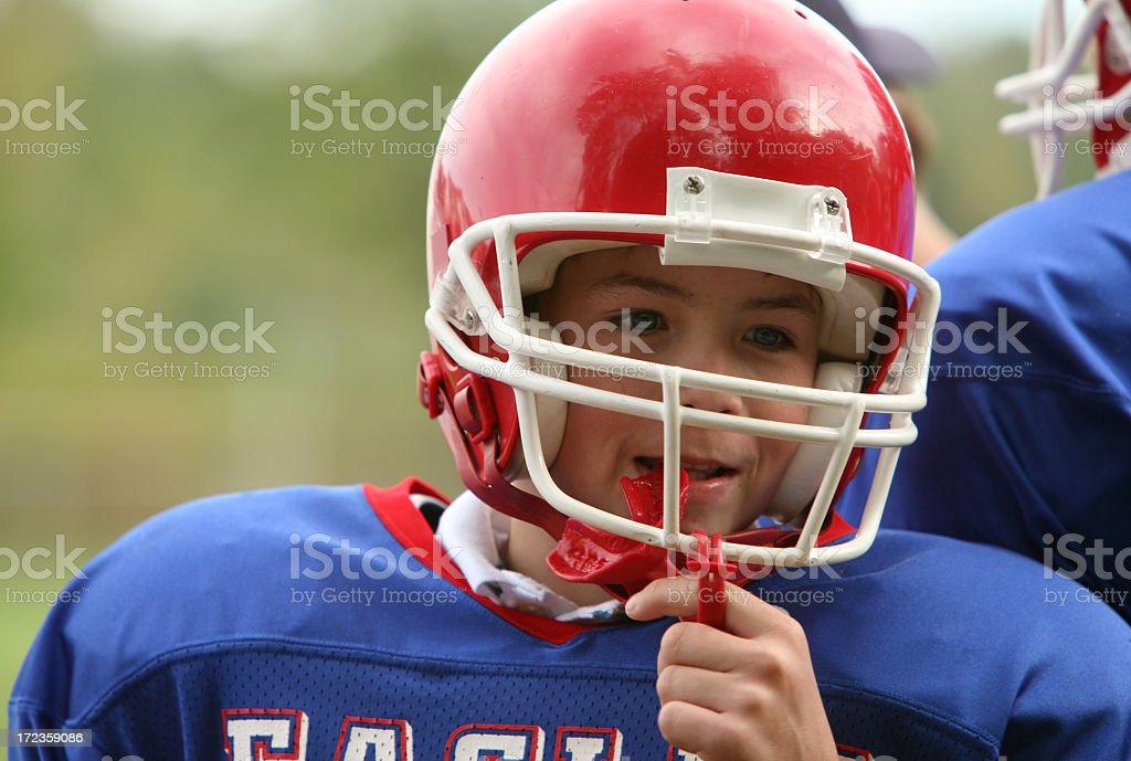 A young boy with an American Football uniform stock photo