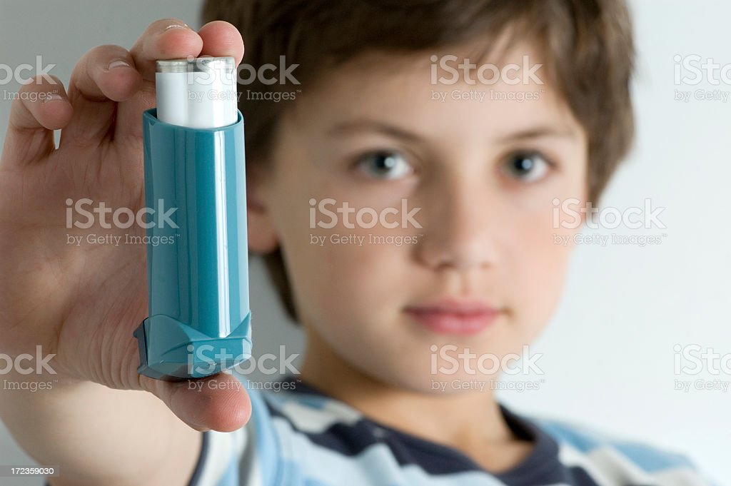 A young boy with asthma holding an inhaler  stock photo