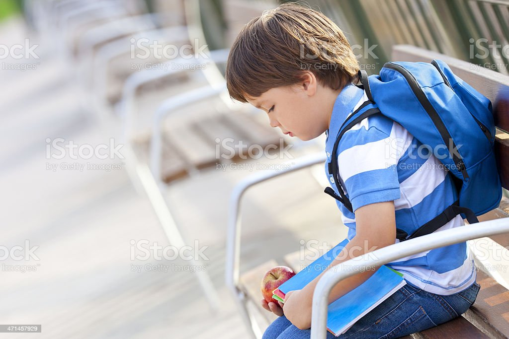 Young boy with blue backpack looking sad stock photo