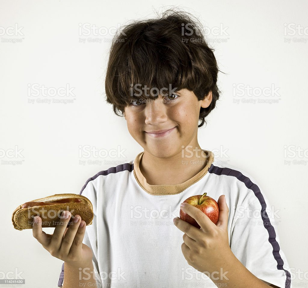 Young boy with brown hair holding a sandwich and apple royalty-free stock photo