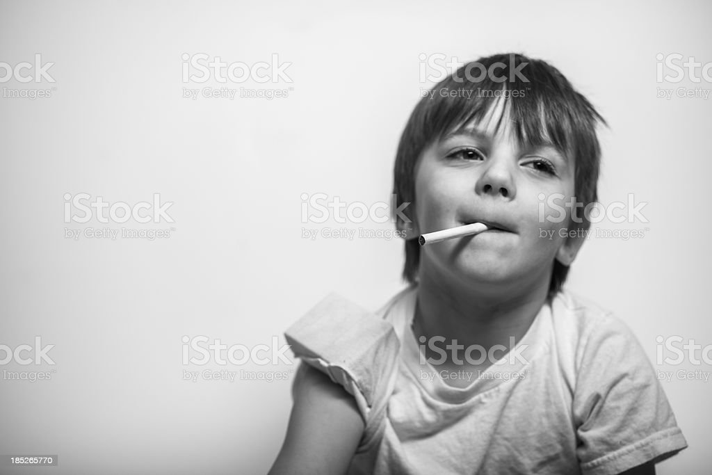 Young Boy with Cigarette in Hand, Looking Away royalty-free stock photo