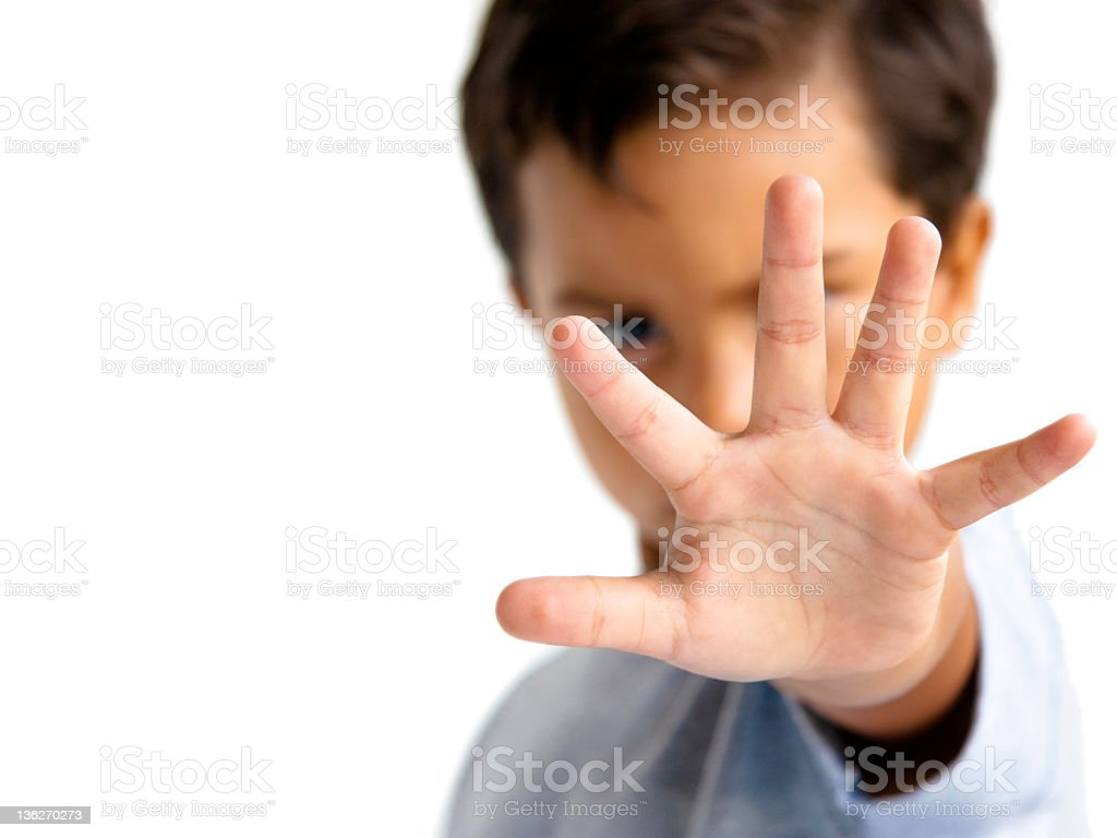 young boy with hand outstretched makes a stop gesture stock photo