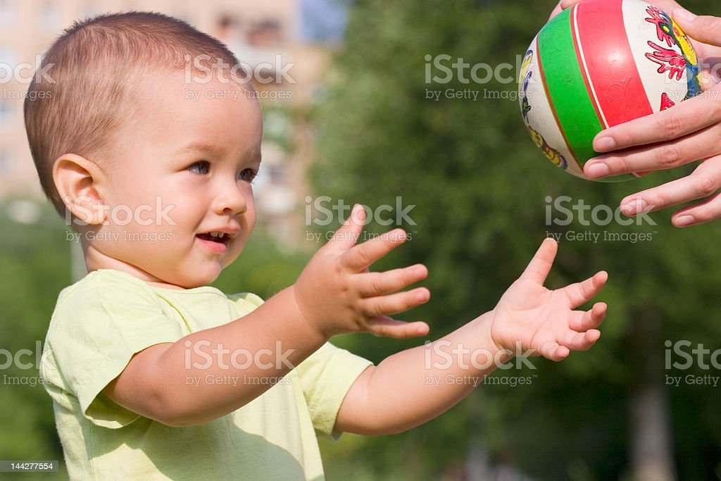 Young boy with his arms extended to get a small ball stock photo