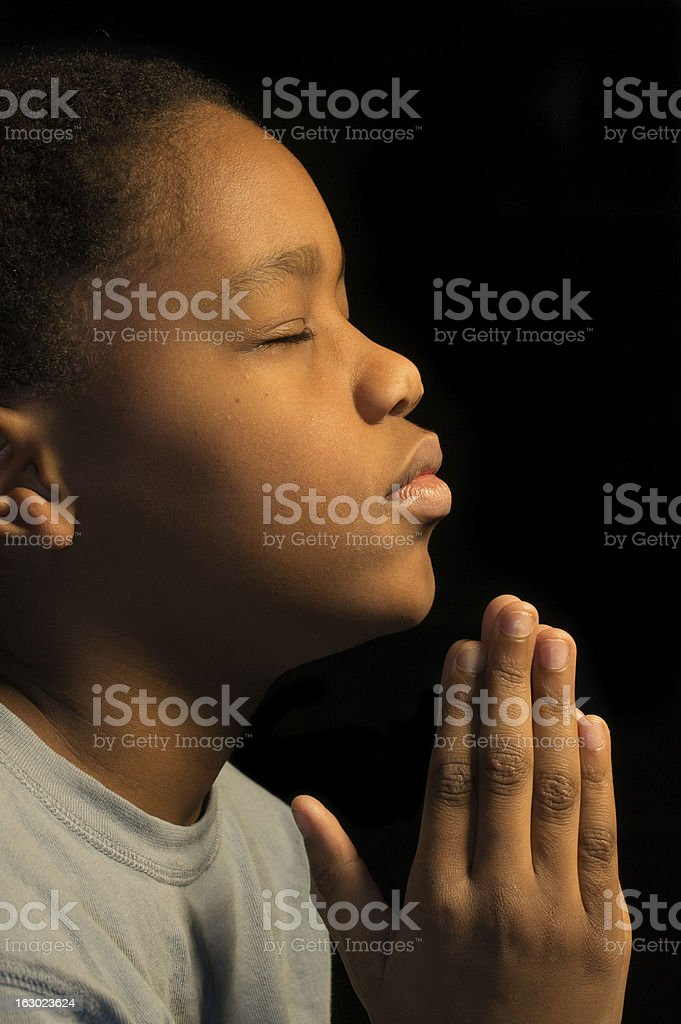 Young boy with his hands held in prayer stock photo