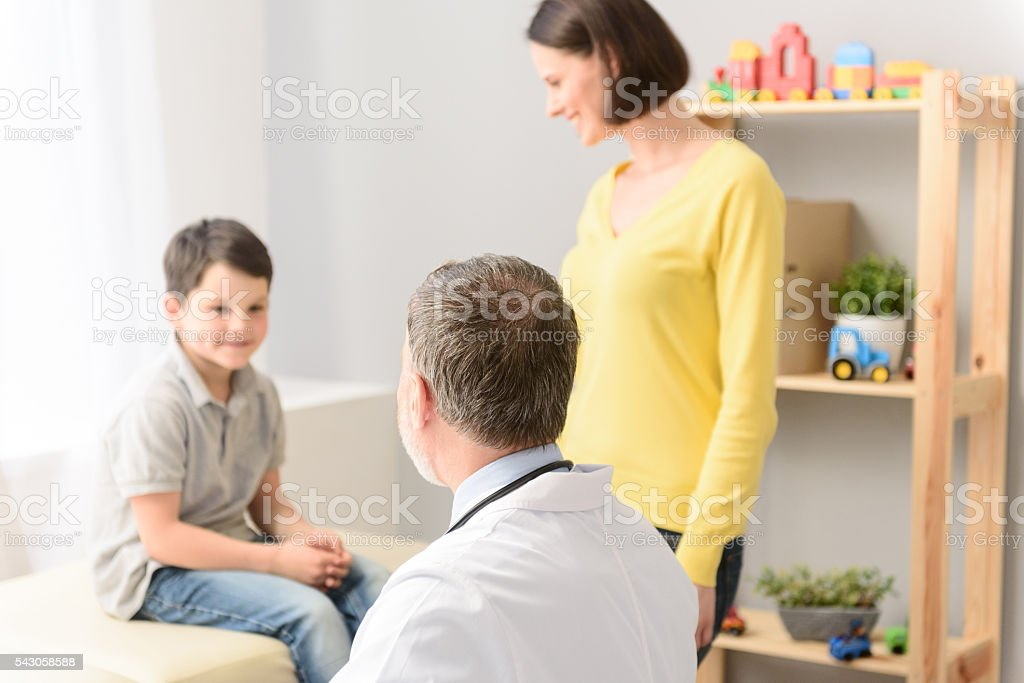 Young boy with his pediatrician and mother stock photo