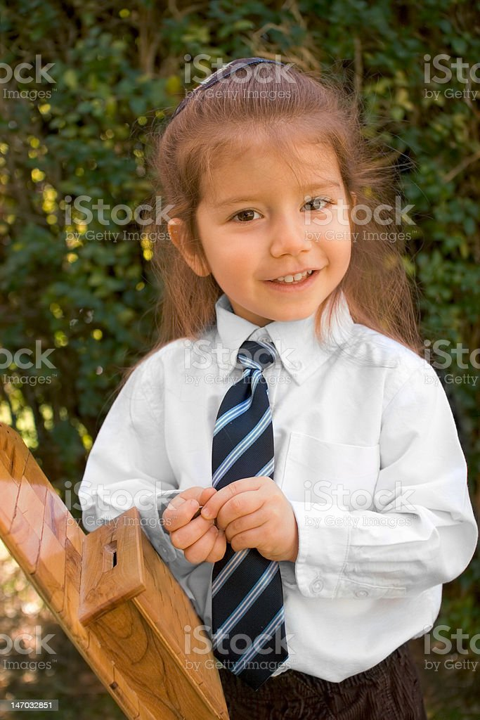 Young boy with long hair in white shirt and tie stock photo