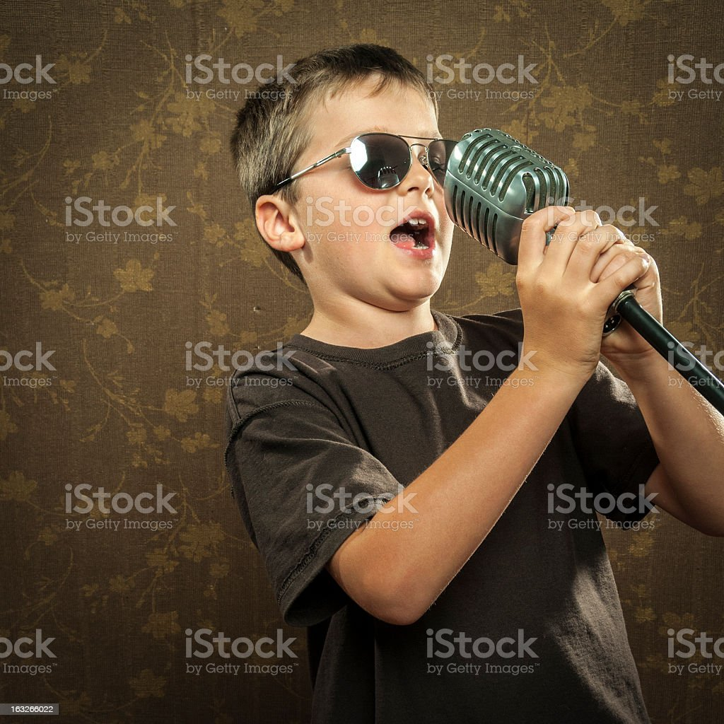 Young boy with microphone singing royalty-free stock photo