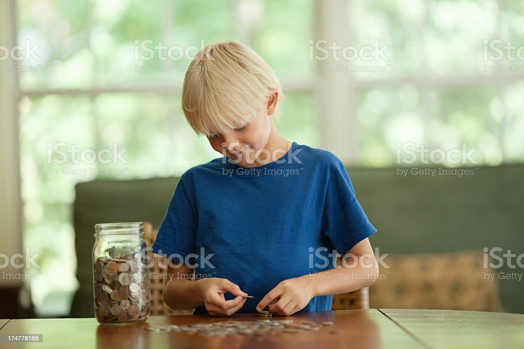 Young boy with money jar counting coins at the table stock photo