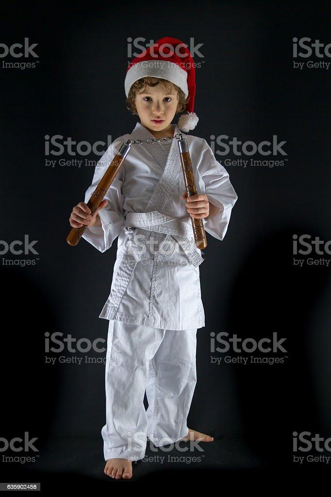Young boy with Santa Hat  practising karate using nunchaku stock photo