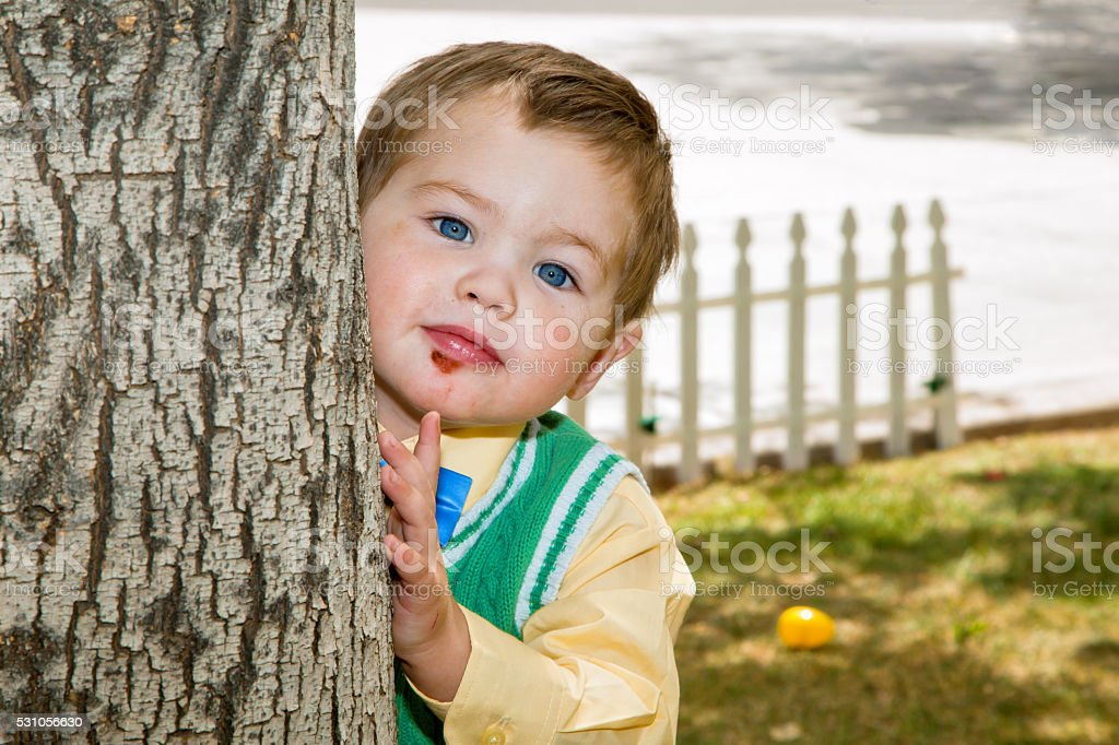 Young Boy With Scabbed Chin Peeks Around Tree stock photo