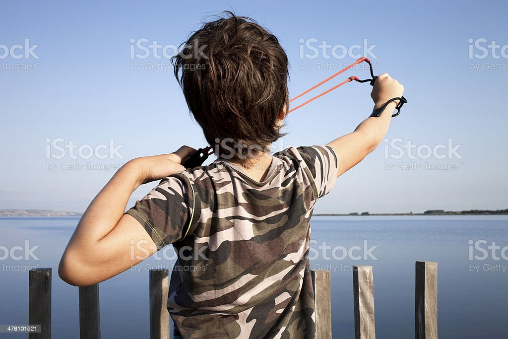 Young boy with slingshot stock photo