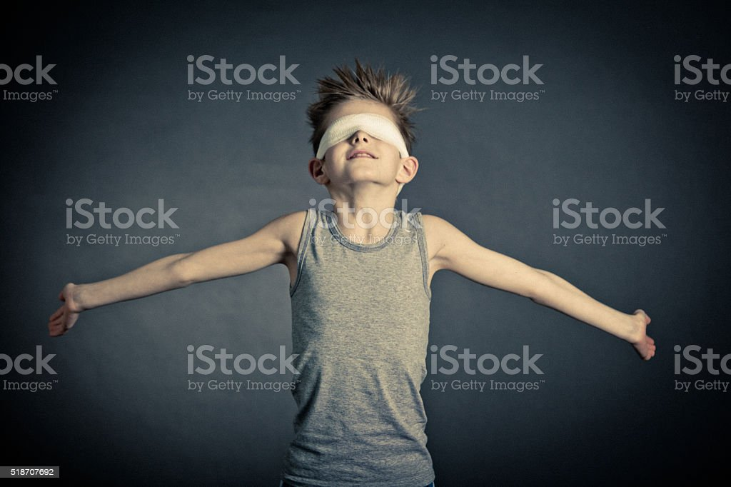 Young Boy with Wide Open Arms and Covered Eyes stock photo