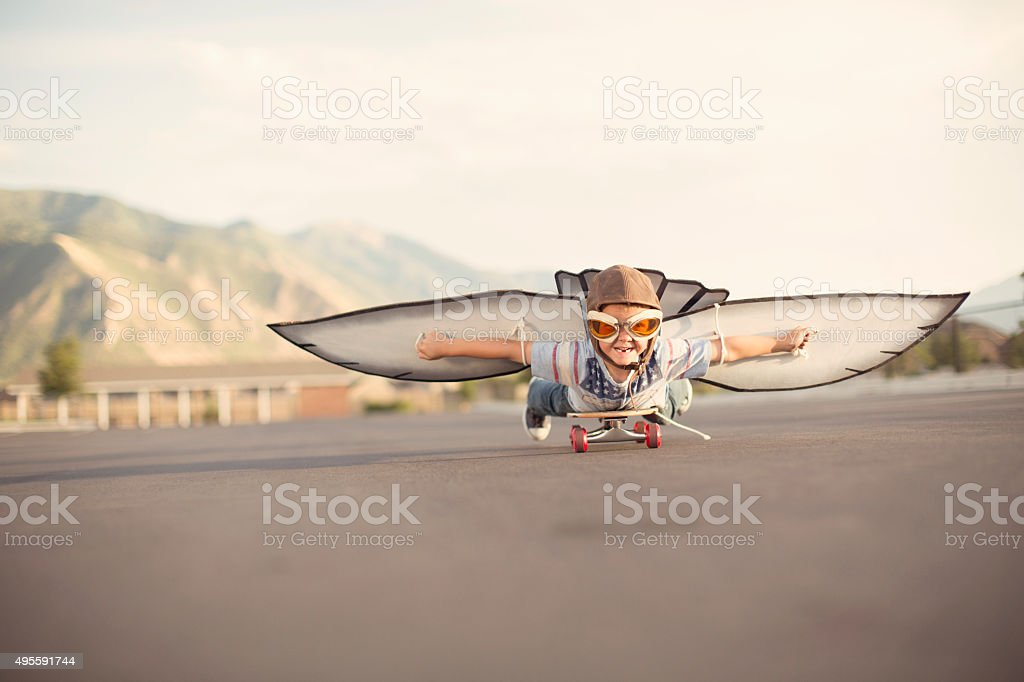 Young Boy with Wings Flies On Skateboard stock photo