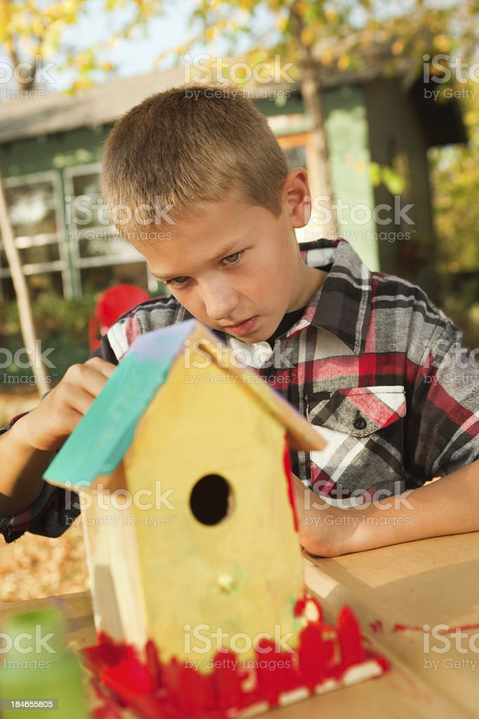 Young Boy Working on Painting Birdhouse royalty-free stock photo
