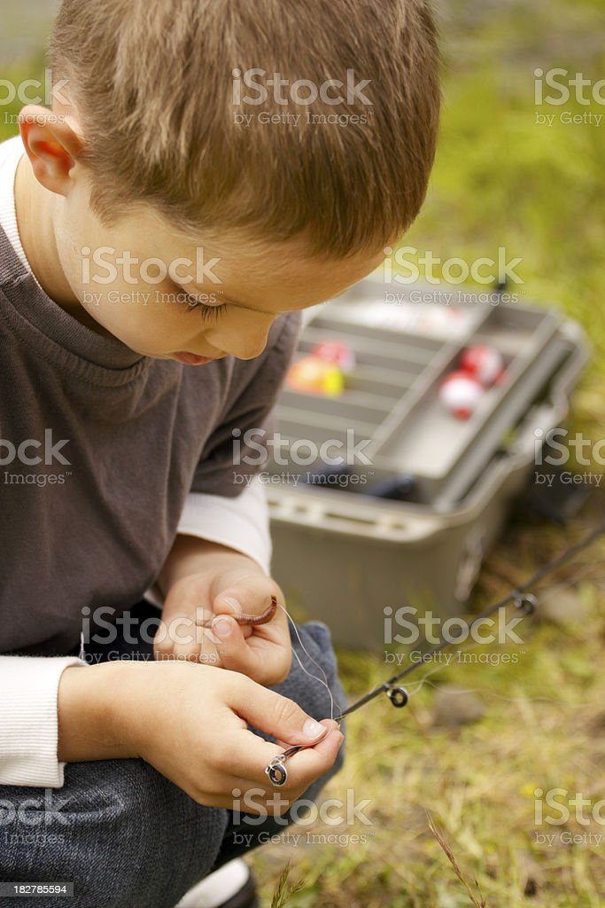 Young boy worming his hook stock photo