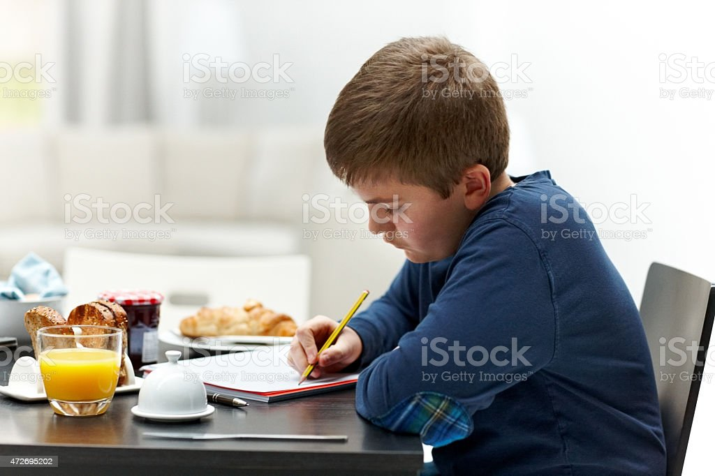 Young boy writing homework at breakfast table stock photo