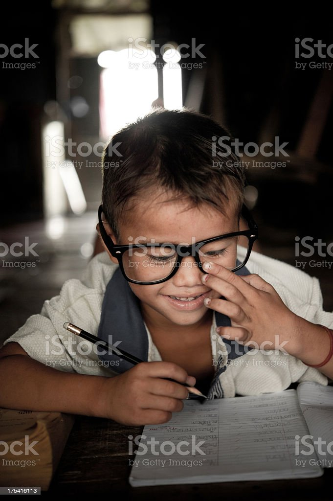 Young boy writing in his journal with oversized glasses stock photo