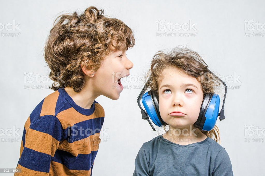 Young boy yelling at sister wearing ear protection stock photo