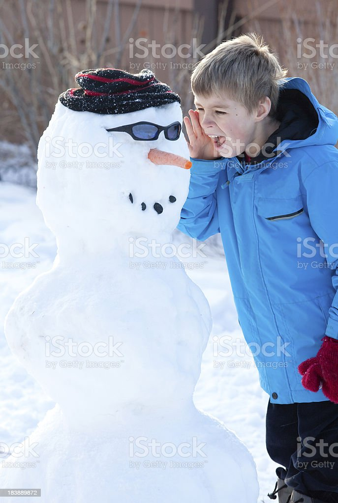 Young Boy Yelling at Snowman stock photo