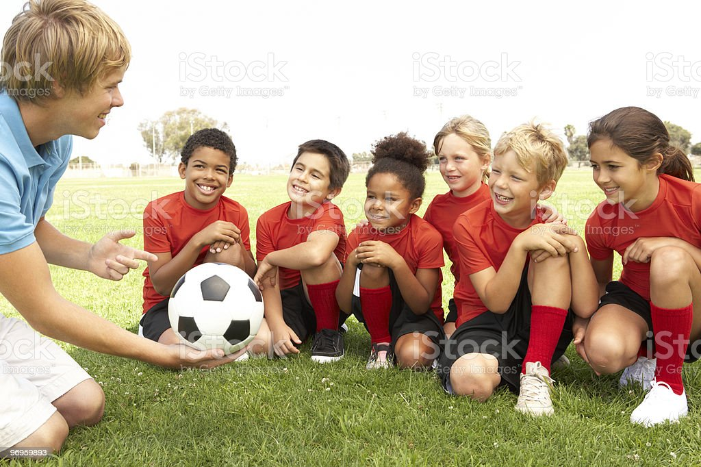 Young Boys And Girls In Football Team  With Coach stock photo
