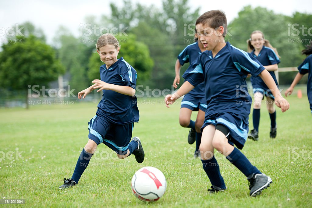 Young boys and girls playing youth soccer on grass royalty-free stock photo