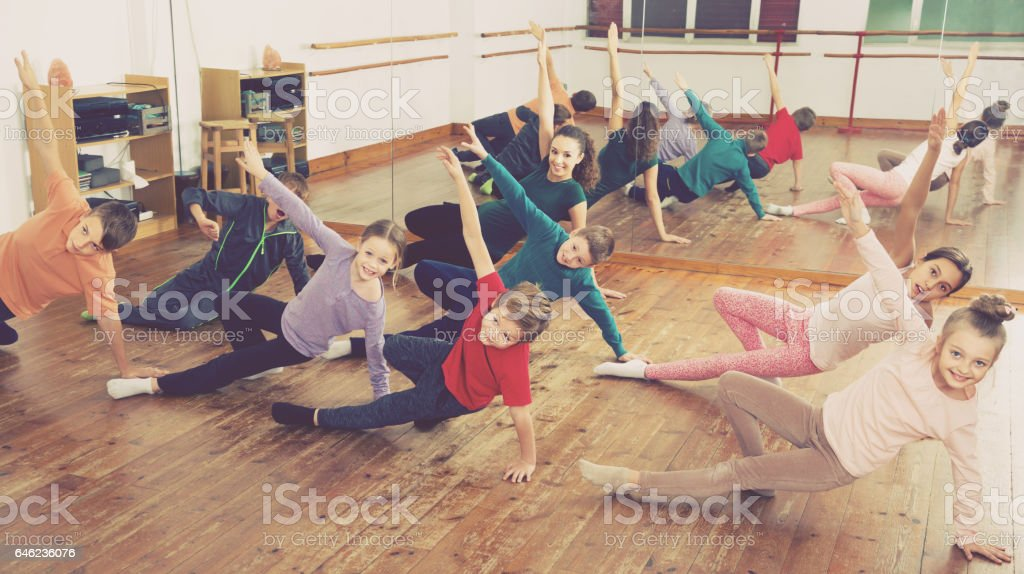 Young boys and girls with trainer stretching in dance hall