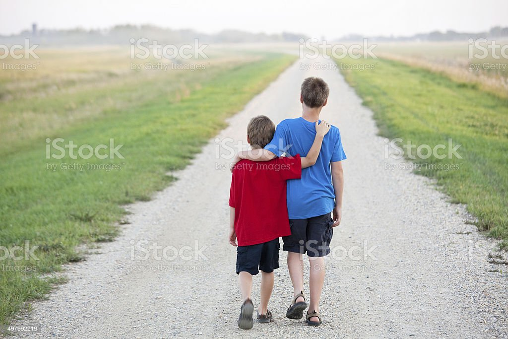 young boys arms around each other walking down road royalty-free stock photo