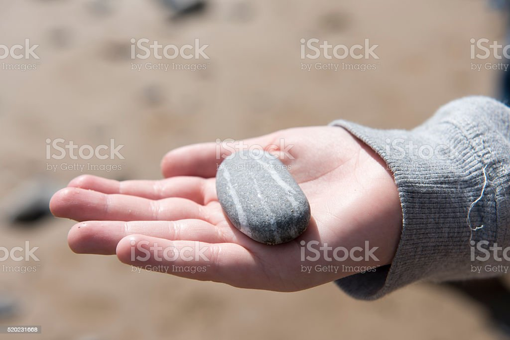 Young boys hand holding pebbles from a beach stock photo