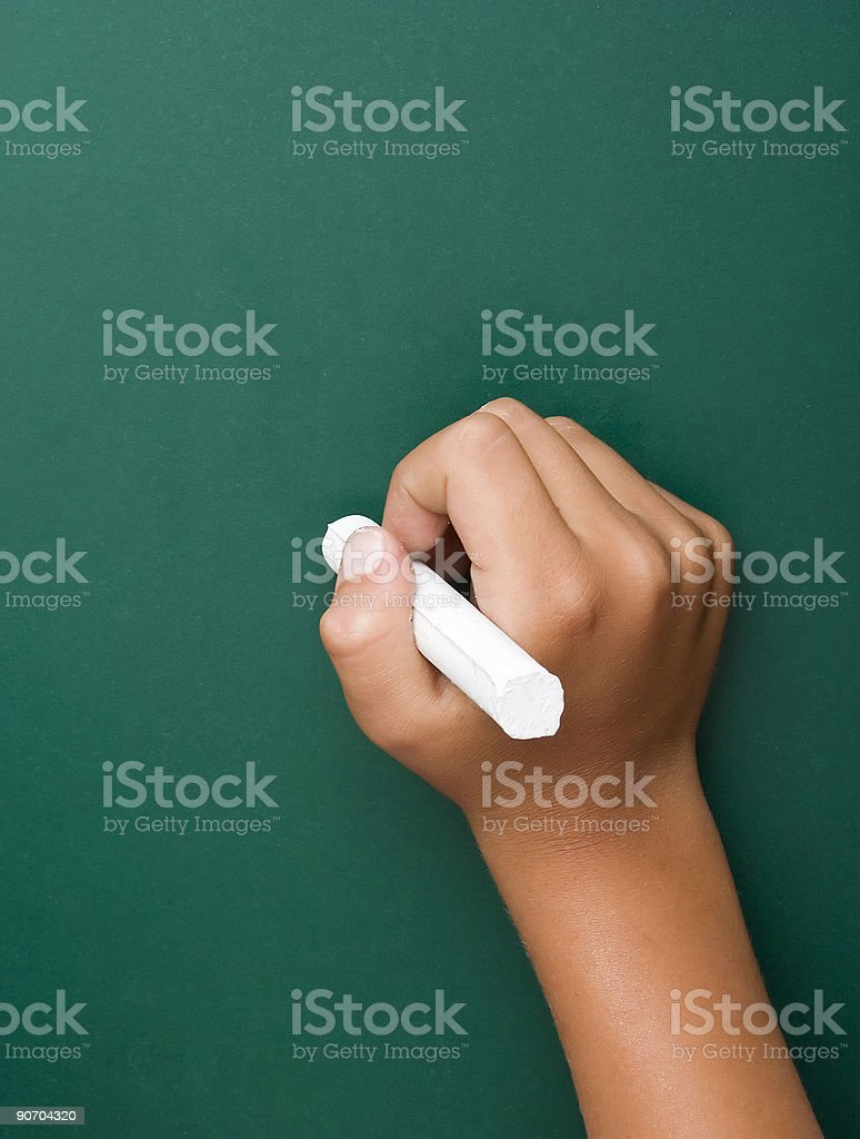 Young boy's hand writing at the chalkboard royalty-free stock photo