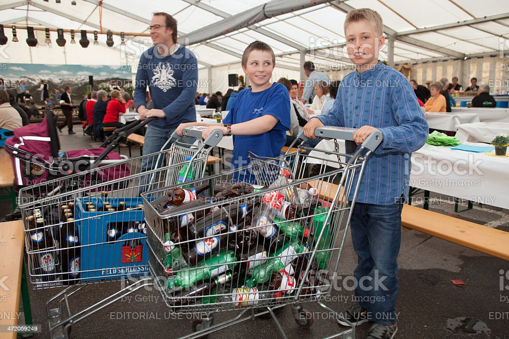 Young boys helping serve at a village festival stock photo