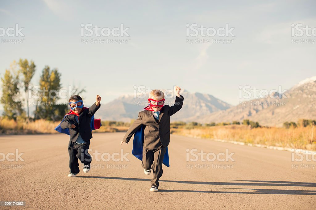 Young Boys in Superhero Costumes and Business Suits are Running stock photo