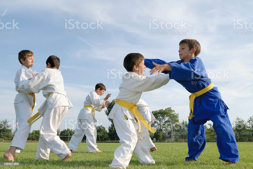 Young boys in white and blue judo gi with yellow belts stock photo