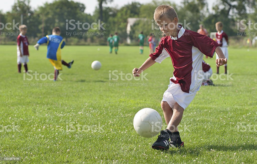 Young boys playing soccer on sports field stock photo