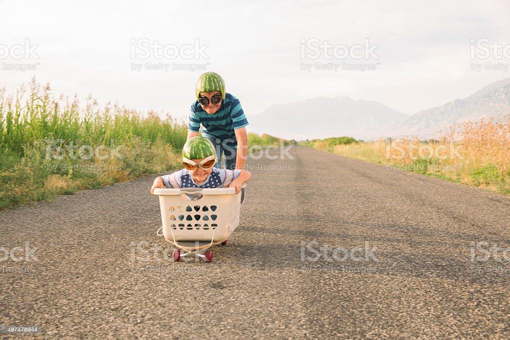 Young Boys Racing on Skateboard Wearing Watermelon Helmets stock photo