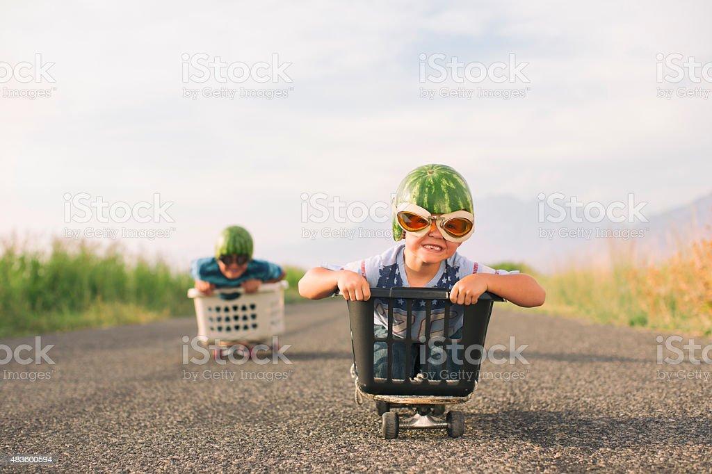 Young Boys Racing Wearing Watermelon Helmets stock photo