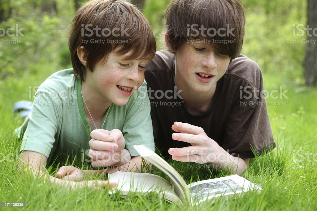 Young boys read a book outside stock photo