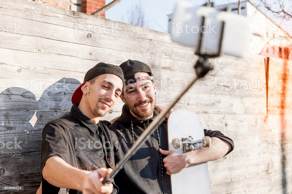 young boys skateboarders takes a selfie outdoor stock photo