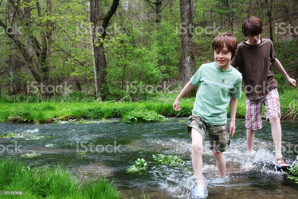 Young boys wading through a stream flowing across a forest stock photo