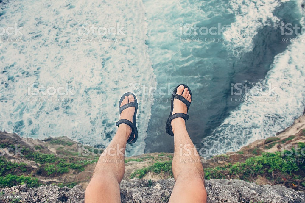 Young brave man sitting on a high cliff stock photo