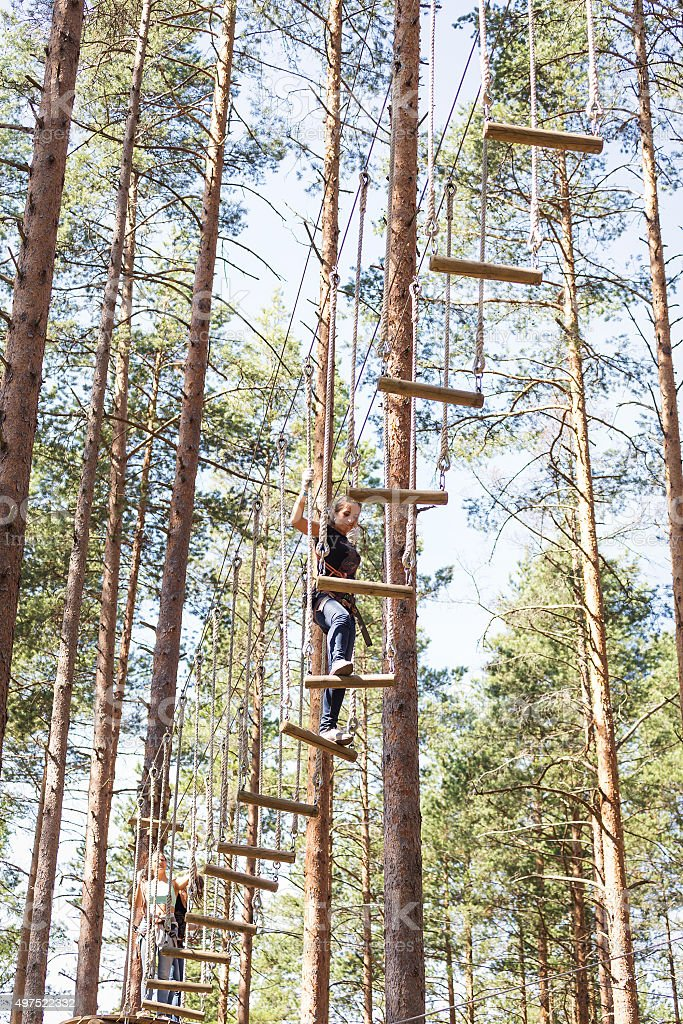 Young brave woman climbing in a adventure rope park stock photo