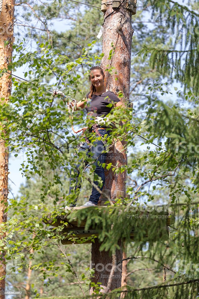 Young brave woman climbing in adventure rope park stock photo