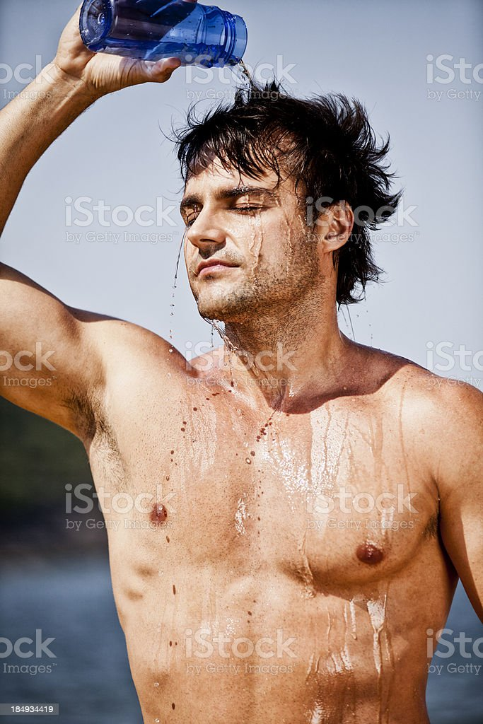 Young brazilian man pouring water on his head after workout royalty-free stock photo