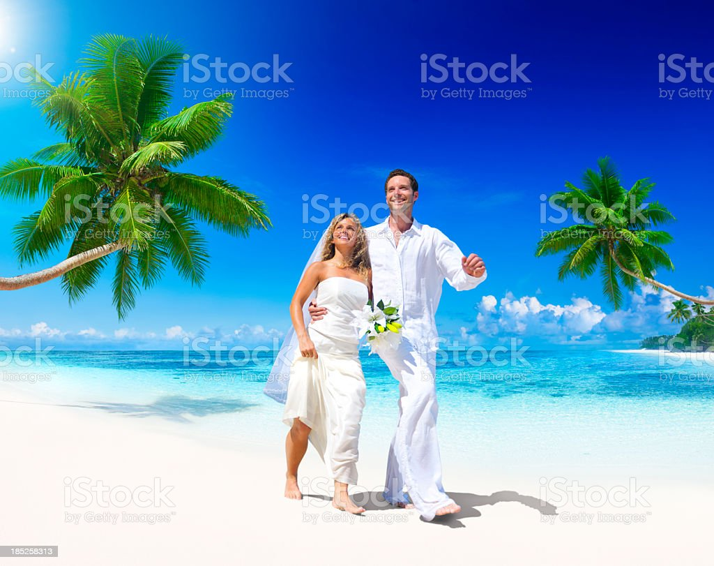 Young bride and groom on a white beach with palm trees royalty-free stock photo
