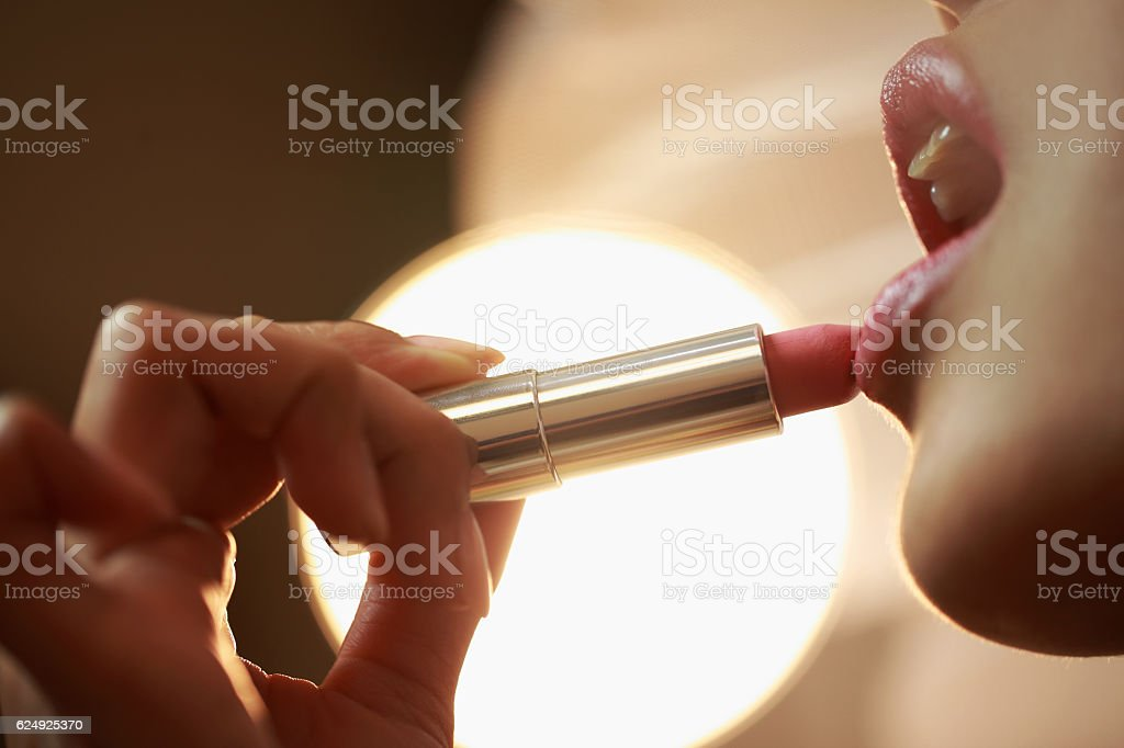 Young bride applying lipstick stock photo