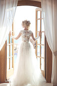 Young bride in gorgeous wedding dress with voluminous skirt