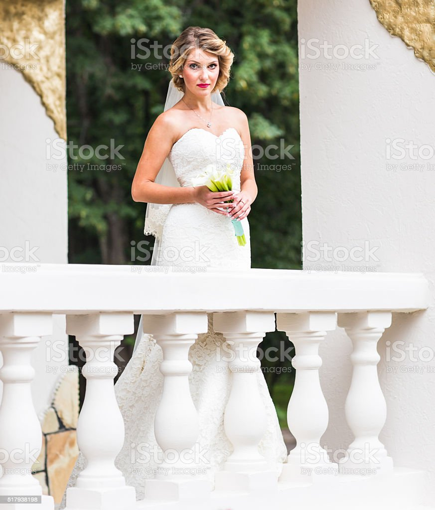 Young bride in wedding dress holding bouquet, outdoors stock photo