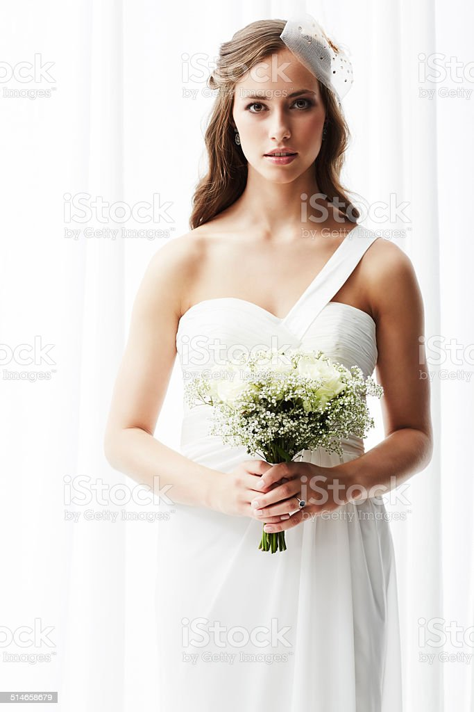 Young bride in wedding dress holding bouquet, portrait stock photo