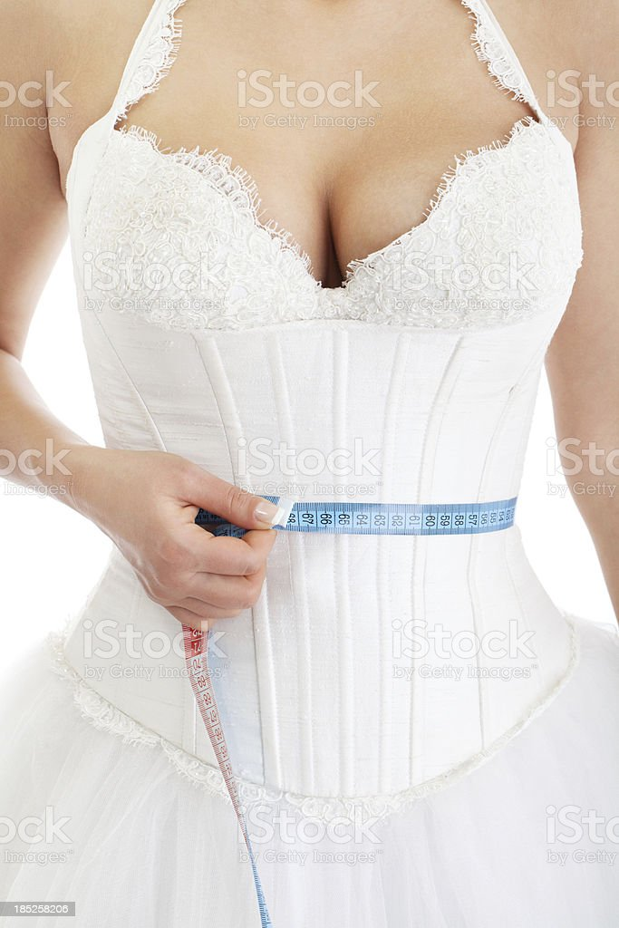 Young bride measuring waist with tape measure royalty-free stock photo